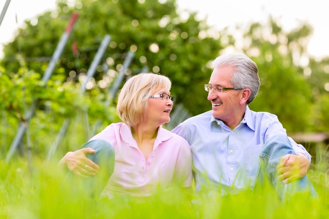 Senior Couple or pensioners, man and woman, sitting in vineyard on summer