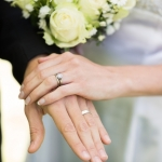 Closeup of bride and groom showing wedding rings touching hands